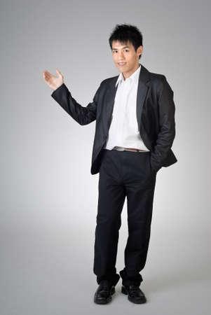 introduced: Hombre de negocios de j�venes introducido sobre fondo gris de estudio.  Foto de archivo