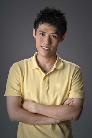 Handsome Asian guy, closeup portrait with smiling expression over studio gray background.
