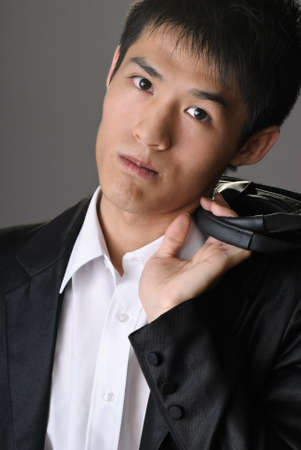 Young attractive business man of Asian holding briefcase on shoulder and looking you. photo