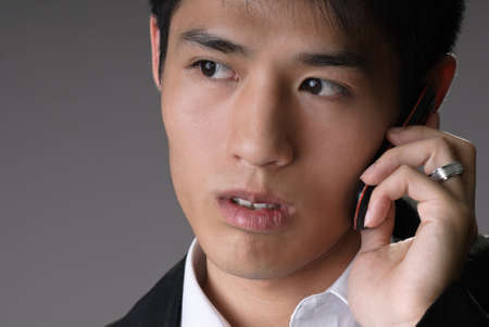 Handsome young business man using cellphone, closeup portrait over studio gray background. photo