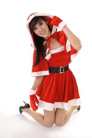 christmas ground: Seductive Christmas beauty of Asian kneel on studio white ground with smile. Stock Photo