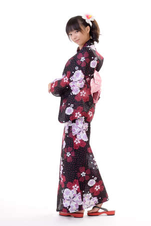 yukata: Attractive Japanese woman with traditional clothing looking and smiling against white. Stock Photo