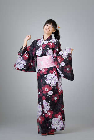 Happy smiling Japanese girl dancing in traditional clothing. photo