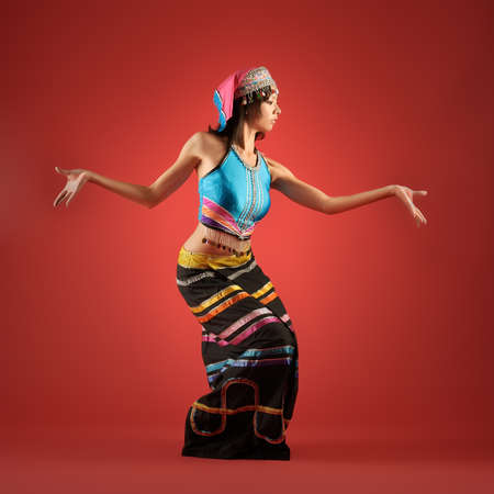 Mysterious China minority nationality girl dancing against red background. photo