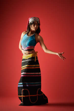 cultural and ethnic clothing: Mysterious dancer of Chinese girl in traditional colorful dress, Dai minority nationality.
