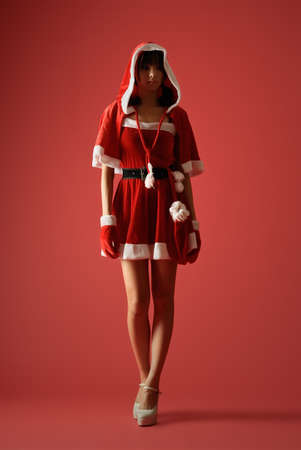 Mysterious Christmas girl in dark over red studio background. photo