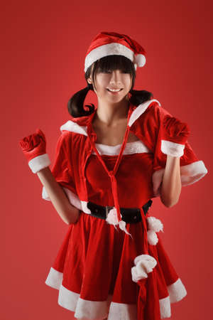 Happy smiling Christmas girl dancing against red background. photo
