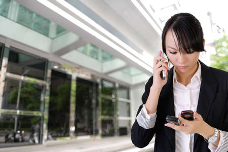 Anxious business woman phone someone and reading SMS outside of office. Stock Photo - 8068284