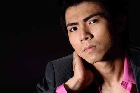 Closeup portrait of Asian young business man against black. photo