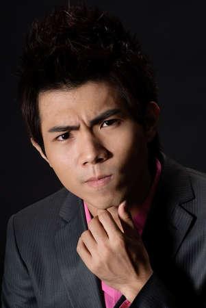 Handsome young business man with contemplative, closeup portrait against black. photo