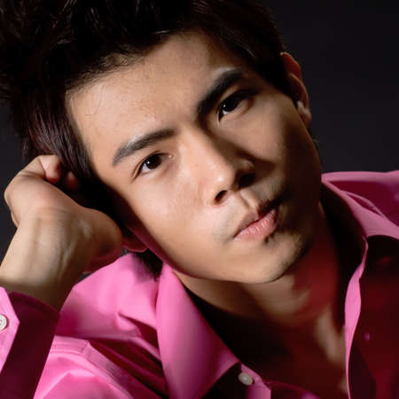 Closeup portrait of young handsome business man of Asian with pondering expression look at you against black. photo