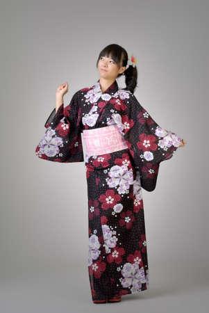 Happy japanese girl dancing, full length portrait in studio gray background. photo