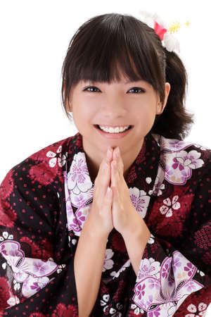 Happy Asian girl praying and smiling with traditional japanese clothes. photo