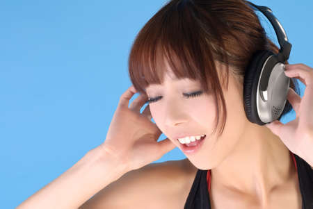 Enchanting young girl of Asian enjoy music over blue background. Stock Photo - 8068549