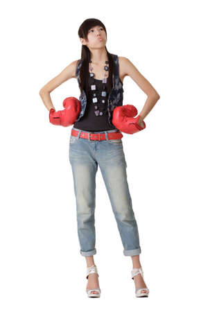 Young woman with boxing gloves standing over white background. photo