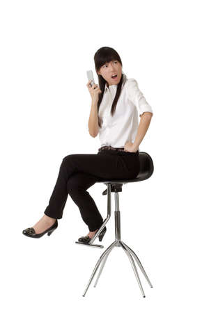 choleric: Angry business woman holding cellphone and siting on chair isolated over white background. Stock Photo