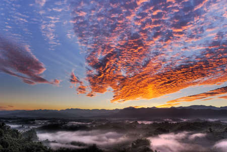 Dramatic cloudscape in morning with red clouds on sky and green mountain in countryside. photo