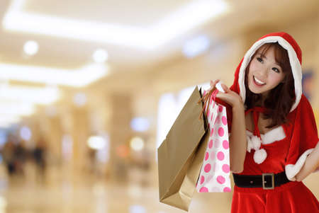 Happy shopping girl wearing Christmas clothes holding bags in department store. Stock Photo