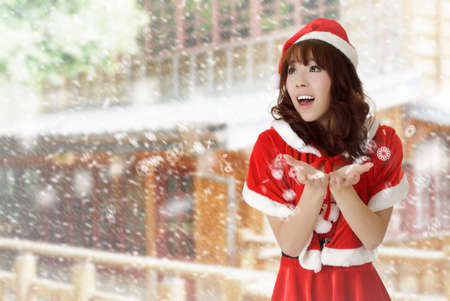 Happy Christmas girl in outdoor with snow falling in winter. photo