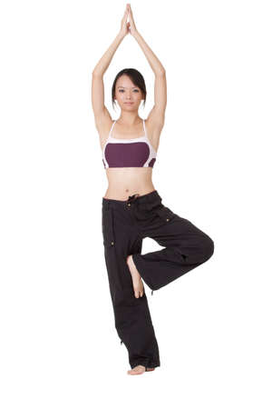 Young woman doing yoga excise by standing on one foot isolated over white. photo
