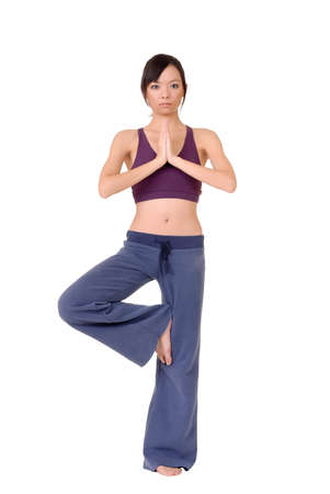 excise: Young woman doing yoga excise by standing on one foot isolated over white.