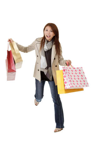 Exciting shopping woman of Asian holding bags isolated over white. Stock Photo - 8285733