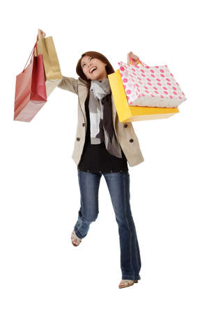Happy shopping woman with exciting expression holding bags isolated over white. photo