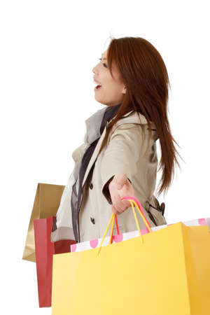 Cheerful shopping woman holding bags and smiling over white. photo
