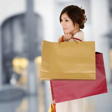Modern woman shopping in mall holding bags and thinking. photo