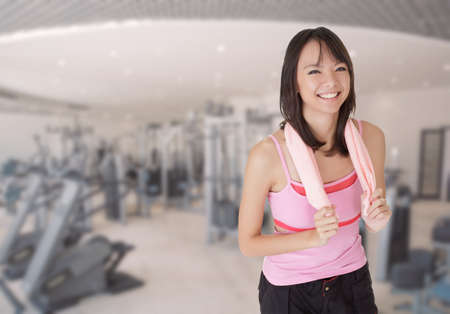 Smiling fit girl holding towel and taking rest in gym. photo
