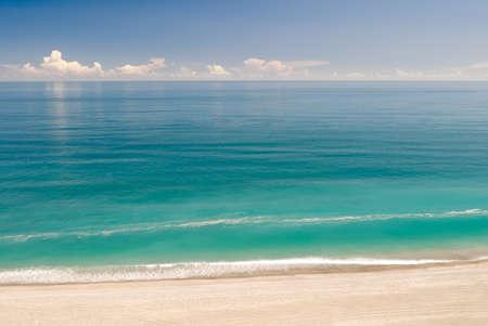 Beach with green ocean water under blue sky.