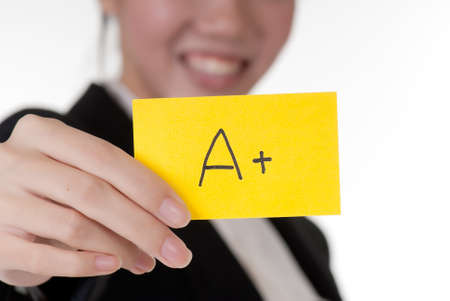 superiority: A+ on business card holding by Asian businesswoman. Stock Photo