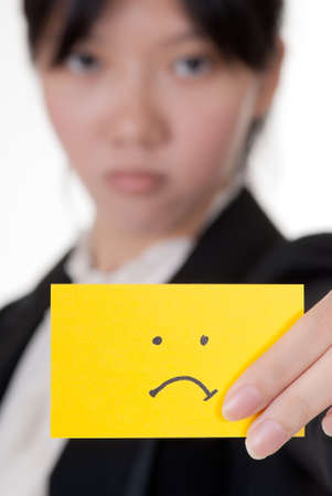 miserable: Unhappy symbol on business card holding by Asian businesswoman. Stock Photo