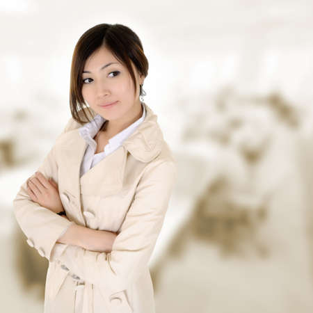Confident business woman with coat thinking in office. Stock Photo - 8437336