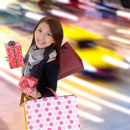 Happy shopping woman in modern colorful city night with cars motion blurred. photo