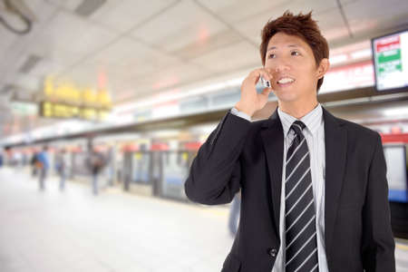 calling communication: Smiling business man using cellphone in station. Stock Photo