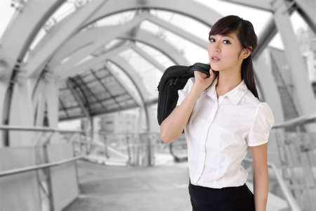 Attractive business woman of Asian holding briefcase inside of modern architecture of flyover. photo