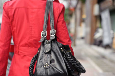 woman holding bag: Single woman holding bag and walking in street, closeup portrait of shallow DOF.