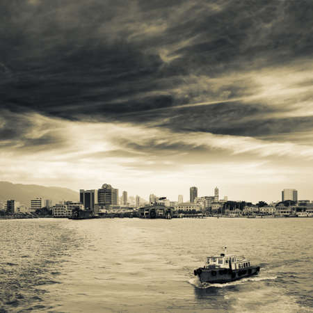 penang: Cityscape of ocean with ship and skyscrapers under dramatic sky in Penang, Malaysia, Asia.