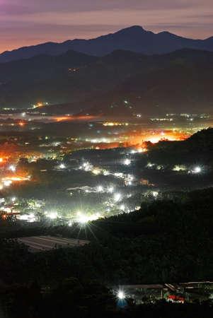 over the hill: Rural nocturna con niebla sobre la colina y edificios.
