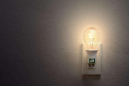 enchufe de luz: Bombilla de luz d�bil y el z�calo en la pared blanca  Foto de archivo