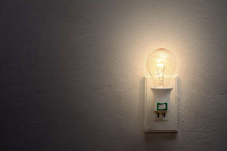 electrical outlet: Weak light bulb and socket on the white wall  Stock Photo