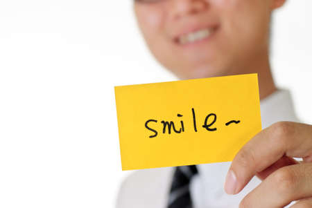 Smile, words on yellow card holding by young man. photo