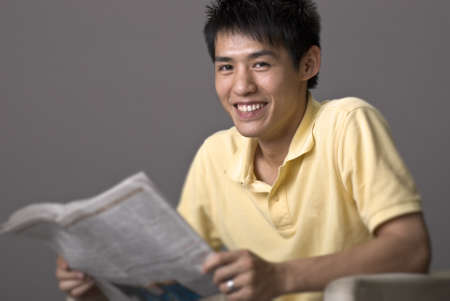 Happy smiling young man of Asian sit and reading newspaper over gray studio background. Stock Photo - 8951978
