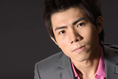 Young business man of Asian, closeup portrait on dark background. photo