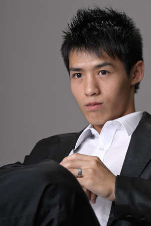 Young business man with confident expression sit on chair, closeup portrait on gray background.