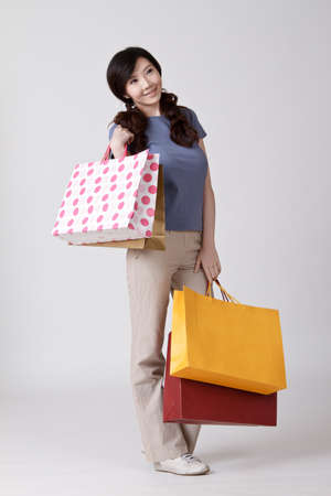 Happy shopping Chinese lady holding bags and smiling. Stock Photo - 8952069