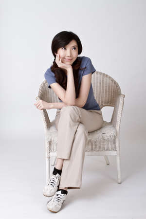 Smiling Chinese woman sit on chair in studio. photo
