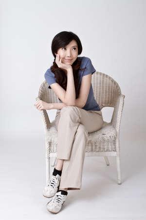 mujer china: Sonriente mujer China de sit en silla en estudio.