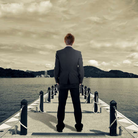Business man standing on dock near lake. photo